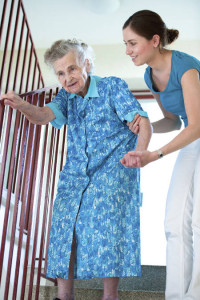 A caregiver with an elderly woman on the stairs