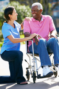 female caregiver with wheelchair bound older man