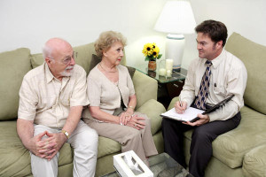 A marriage counselor or services meeting with a senior couple. The wife is receptive but the husband looks skeptical
