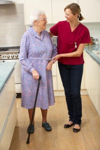 woman-in-kitchen-with-cane-and-caregiver
